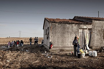 Michele Palazzi & Alessandro Penso: A Migrant Washing his Clothes, Basilicata, Italy